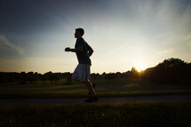 man running outdoors at sunset