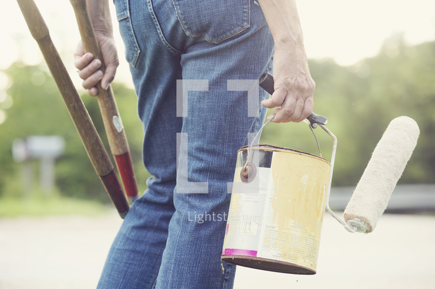 man carrying tools and paint supplies