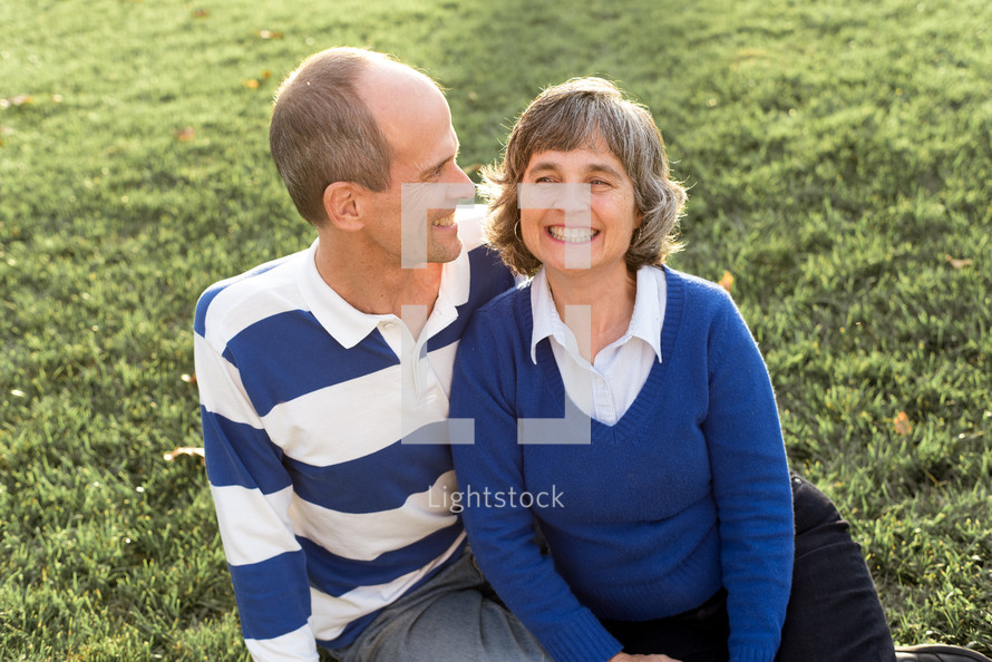 a couple sitting in grass