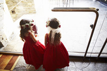 flowers girls looking out a glass door