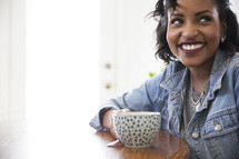 an African American woman sitting at a table with a coffee cup