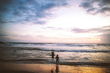 children at the beach at sunset
