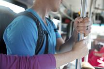 people holding onto a pole riding a city bus.
