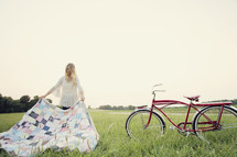 young woman setting up a blanket in the grass standing next to her bicycle