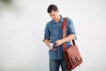 a man standing with a messenger bag reading a Bible