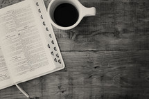 open Bible on a table and a cup of coffee