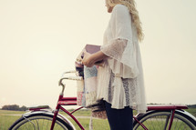 young woman standing next to a bicycle holding a quilt and a bible.