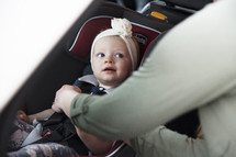 a mother fastening her toddler daughter into her carseat