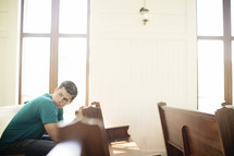 Man looking over his shoulder while praying in a church pew.
