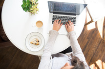 woman typing on a laptop computer with coffee and pastry on the table