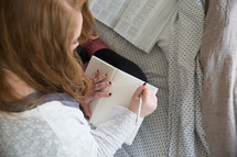girl reading a Bible and writing in a journal on a bed