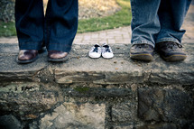 shoes on a man and woman standing next to empty baby shoes