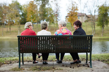 elderly women sitting on a park bench talking