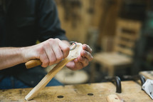 man carving wood