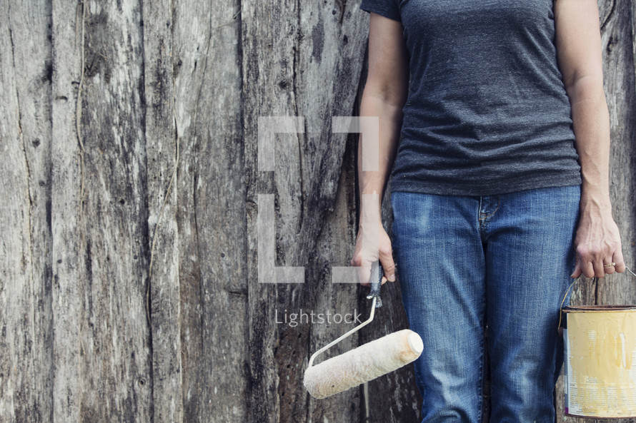 woman holding a paint bucket and paint roller in front of an old wood building.