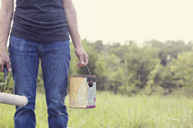 man holding a paint bucket and paint roller