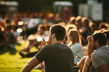 people sitting in the grass at an outdoor christian music concert