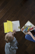 a toddler boy and girl reading a book on the floor