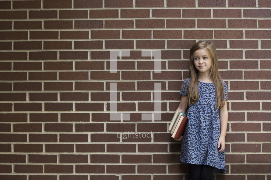a young girl holding books standing in front of a brick wall
