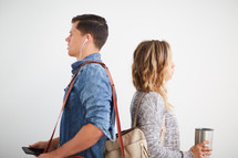 a man and woman standing listening to earbuds