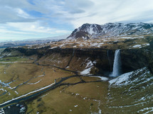 aerial view over a waterfall and snow capped mountain