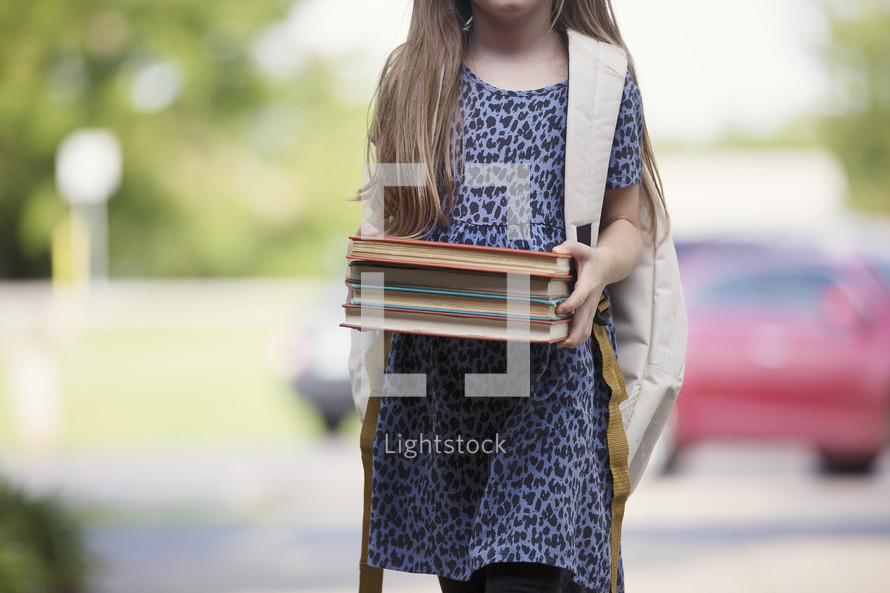 a young girl holding books walking to school
