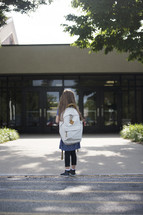 A little girl with a backpack looking at the front doors of a school.