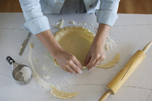 Hands preparing a pie crust for baking.