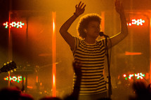 woman singing into a microphone with raised hands