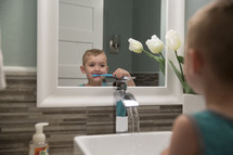 child brushing his teeth at the sink
