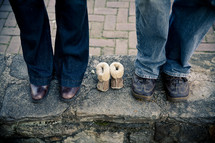 expectant parents standing beside empty baby shoes
