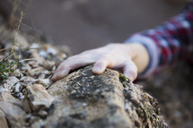 hand reaching to grab onto a rock