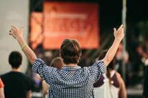 man with his hands raised in worship at an outdoor concert