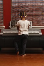 girl child playing a digital piano