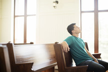 Man looking up while praying in a church pew.