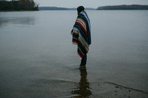 man wrapped in a blanket standing in water