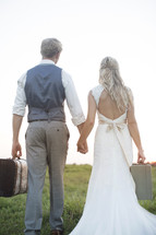 bride and groom carrying luggage