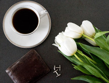 leather wallet, coffee cup and saucer, and tulips on a table