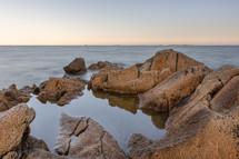 tide pool between rocks on a beach