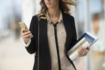 A businesswoman looking at her cell phone.