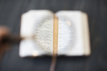 magnifying glass on the pages of a Bible