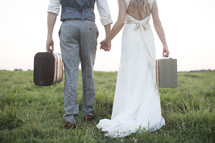 bride and groom carrying luggage in an open field.