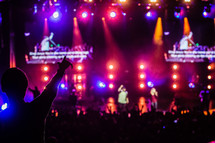 a band on stage surrounding by fans in the audience