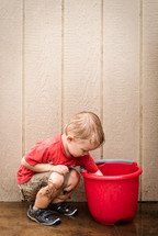 a toddler boy playing in a bucket of water