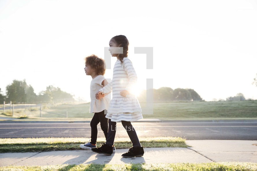 young sisters walking holding hands down a sidewalk.