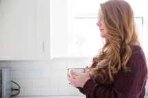 woman in thought holding a mug of coffee