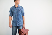 man holding a messenger bag looking to the side
