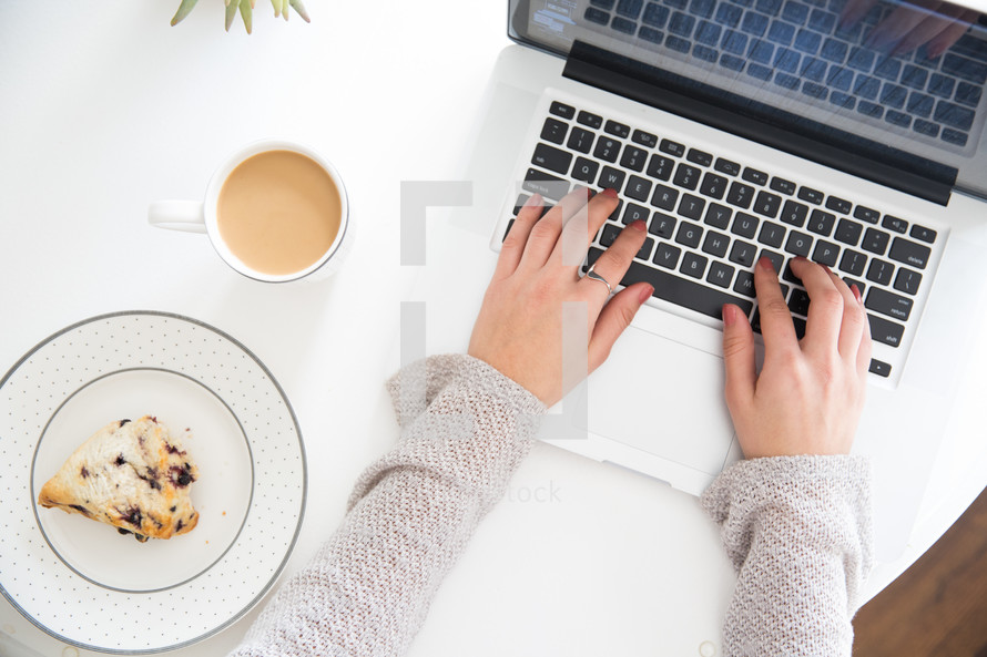 woman typing on a laptop computer and coffee and a pastry on the table