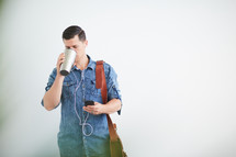 a man standing holding a messenger bag listening to earbuds and drinking coffee