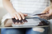 a woman holding a credit card and shopping online